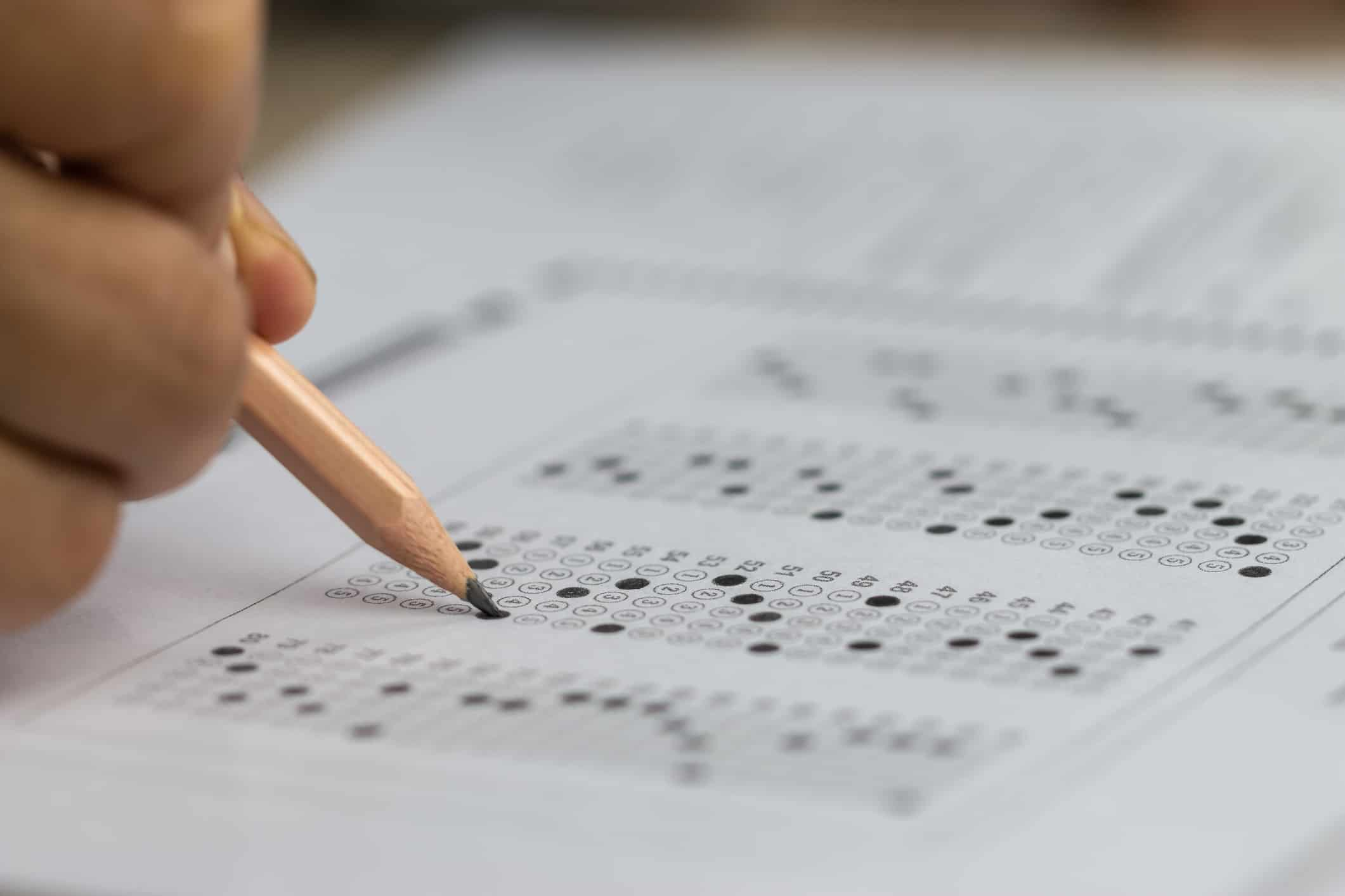 Student filling out a test with pencil
